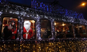 A man dressed as Santa Claus and a woman dressed as mythical creature Krampus travel in a tram decorated with Christmas lights in the centre of Budapest.