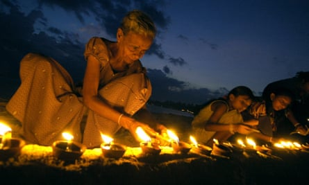 A Sri Lankan woman lights an earthenware lamp as she sits with others at Unawatuna Beach in Galle, some 123 km south of Colombo, 26 January 2005.  Sri Lankans lit some 40,000 lamps in memories of those killed by tsunami waves which struck 26 December 2004