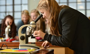 Schoolgirls using microscopes during a science lesson