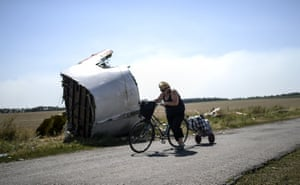 A woman walks with her bicycle past wreckage of flight MH17 in the village of Hrabove