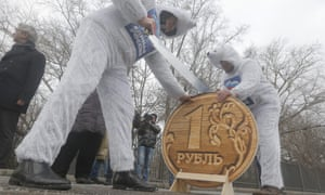 Communist party activists saw through a replica of the Russian rouble at an anti-government protest in Moscow on Monday.  EPA/MAXIM SHIPENKOV