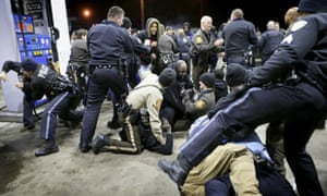 Police try to control a crowd, on the lot of a gas station following a shooting in Berkeley, Missouri.