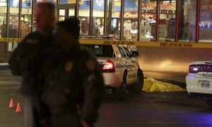 Police stand guard following a shooting Tuesday at a gas station in Berkeley, Missouri