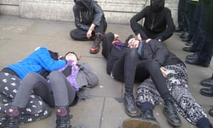 Protesters lie on the ground next to police outside the old RBS building near Trafalgar Square.