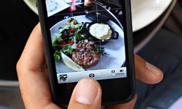 A man takes a picture with his mobile of food on his plate.