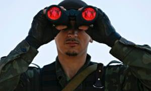 A pro-Russian separatist looks through binoculars