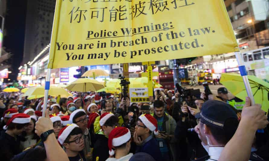 Hong Kong police hold up a warning banner as pro-democracy protesters fill a street and sing Christmas songs.