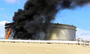 Black smoke billows out of an oil tank