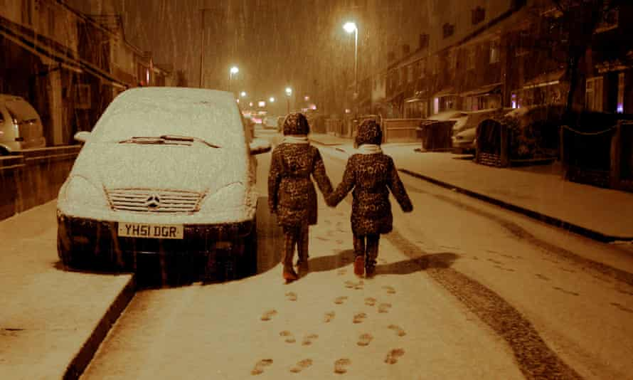 Maisy Byrne, nine, (left) and sister Lulu, seven, have fun as snow falls on Boxing Day in Gateacre, Liverpool.