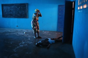 Umu Fambulle stands over her husband Ibrahim after he staggered and fell, knocking him unconscious in an Ebola ward in Monrovia, Liberia on 15 August 2014.