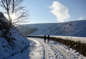 A couple walk along an untreated, snow-covered road past Butterley Reservoir near the village of Marsden, northern England.