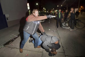 A plainclothes detective, who had been marching with anti-police demonstrators, aims his gun at protesters after some in the crowd identified him  in Oakland, California, on 10 December 2014.
