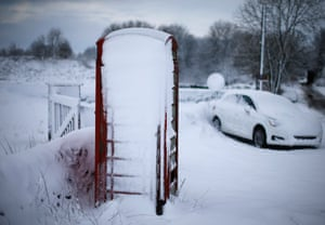An abandoned car and a telephone box stand in snow near Ashbourne, central England.