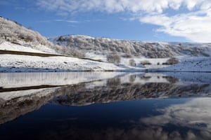 Snow-covered fields and trees are reflected in Butterley Reservoir.