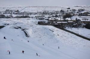 Children sledge down the in the village of Marsden.