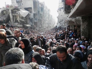 Residents emerge to receive food aid distributed by the UN Relief and Works Agency at the besieged al-Yarmouk camp in Syria on 31 January 2014