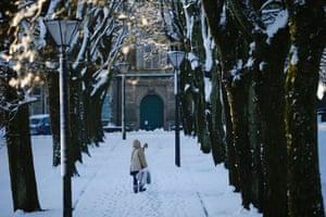 A woman walks through snow in Buxton.