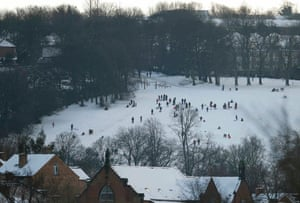 People sledge in a snow covered park in Sheffield.