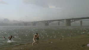 People run for shelter from a hailstorm on the beach at the river Ob in Siberia, Russia, on 12 July 2014.