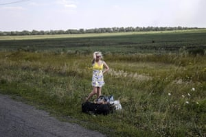 A woman cries as she stands on the road with her luggage after she left her home near the village of Hrabove, Ukraine, on 2 August 2014.