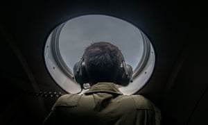 A member of the Indonesian military looks out of the window during a search and rescue (SAR) operation for missing Malaysian air carrier AirAsia flight QZ8501, over the waters of the Java Sea on December 29, 2014.