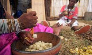 Women crush marula kernels