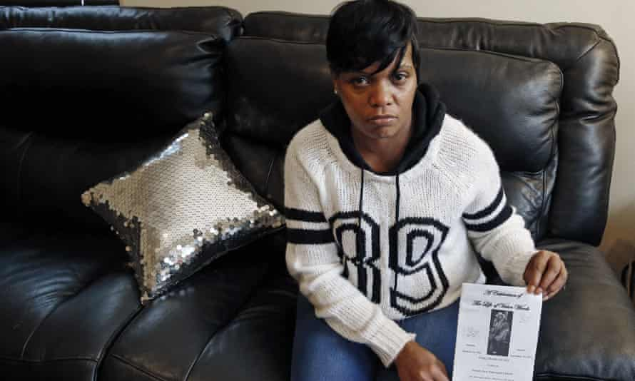 Terri Scroggins holds a memorial program for her fiance, Victor Woods, in Boston. Woods died 1 October and a video shows him convulsing as inmates held him and a guard watched.