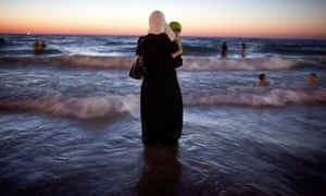 A Palestinian woman dressed from head to toe stands in the sea holding her baby as others swim