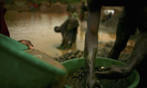 Sifting through buckets of dirt looking for gold in Mongbwalu, DRC.