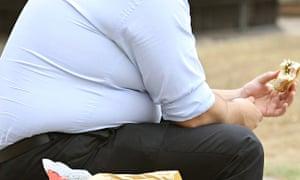 overweight man eating a sandwich