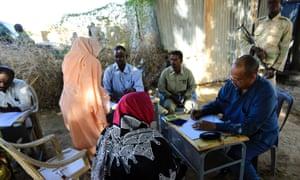 达尔富尔犯罪问题特别检察官调查塔比特村的大规模强奸指控,两侧是武装人员。