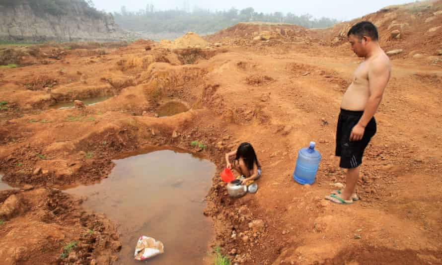 This picture taken on July 30, 2014 shows a girl and her father collecting water from an almost dried up resevoir, two kilometers from their home, in Pingdingshan, central China's Henan province. Severe drought and scorching heat has damaged over a million hectares of farmland in China's Henan and Inner Mongolia provinces, with no immediate relief in sight, a state news agency reported.