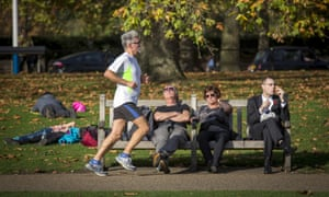 A runner passes people sitting on a bench in the sunshine in Green Park on October 31, 2014 in London, England.  Temperatures in London are forecasted to exceed 20 degrees making today the hottest Halloween on record.