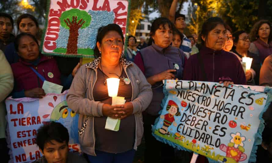 Hundred of participants attend a candlelight vigil, a day before the inauguration of this year's climate change conference in Lima, Peru.
