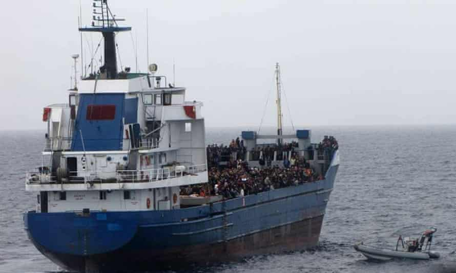 A boat with migrants is towed by an Italian military ship off the coast of Sicily.