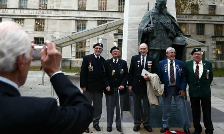 Veterans have their photograph taken next to the memorial following the unveiling ceremony.