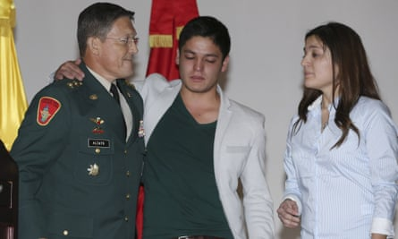 General Ruben Alzate, left, embraces his son Juan Pablo after reading a statement at the military hospital in Bogota on Monday.