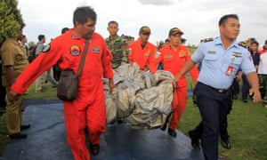 Indonesian air force crew members carry what is believed to be an emergency slide from the AirAsia plane.
