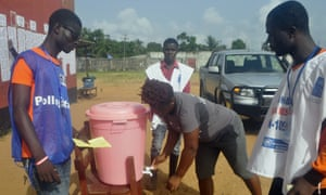 Health workers man a polling station in Liberia during a twice-delayed senate vote that was criticised for its potential to spread Ebola
