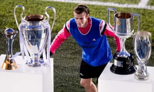 Real Madrid's Gareth Bale poses with the club's trophies during a training session.