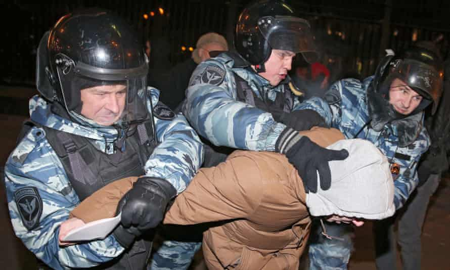 A group of police officers detain one of Alexei Navalny's supporters at the rally.