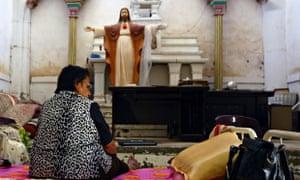 An Iraqi Christian woman sits inside a church in Telkaif near Mosul