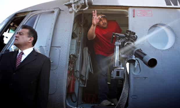 Vigilante leader Luis Antonio Torres waves from inside a military helicopter