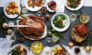 Festive fare on a packed Christmas table: a festive slow-roast honey goose, perfect roast potatoes, kale with toasted brazil nuts and bacon, a walnut and apricot stuffing loaf, and whole shallots with red wine.