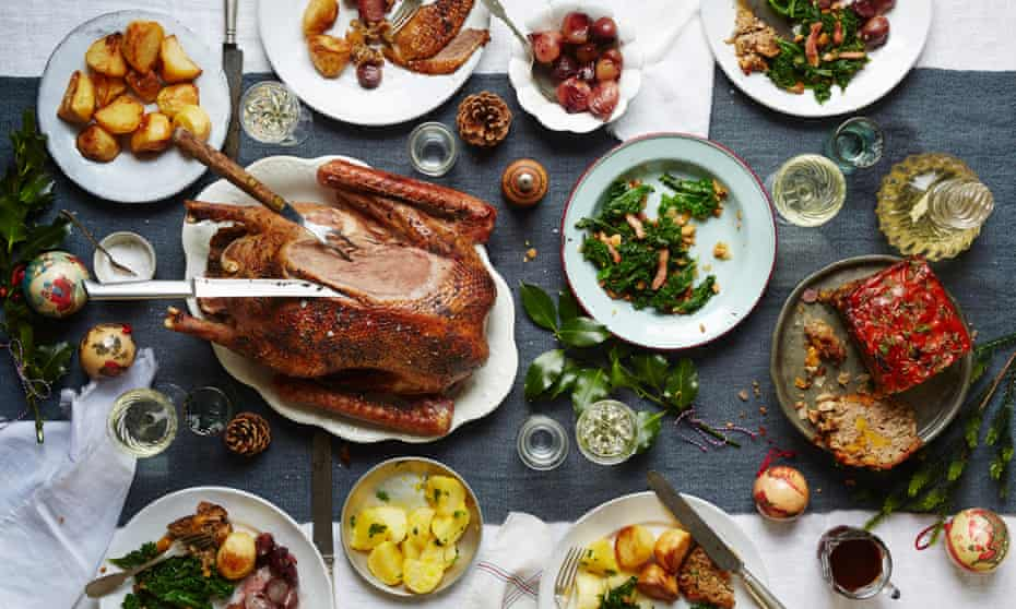 Festive fare on a packed Christmas table: a festive slow-roast honey goose, perfect roast potatoes, kale with toasted brazil nutsand bacon, a walnut and apricot stuffing loaf, and whole shallots with red wine.