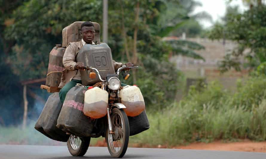 Man carrying oil on his motorcycle