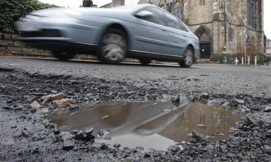 Car drives past a big pothole