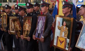 Thai soldiers hold portraits of the king for a ceremony marking his birthday.