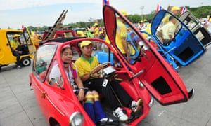 People pose with vintage cars during the typically colourful royal birthday celebrations.