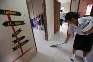 An older student who attends the nearby high school but lives at Yaowawit sweeps the floor of her room